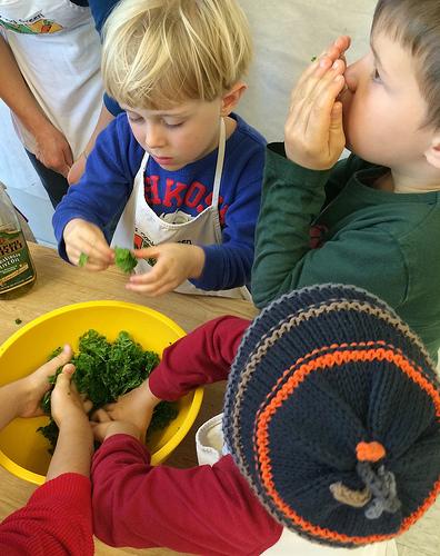 Kids making kale salad by massaging in olive oil via LizsHealthyTable.com